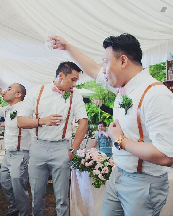 Caballeros de honor en pajaritas rosas y padrinos del novio en corbatín gris. Tiradores en cuero color tostado y una boutonniere botánica vintage.