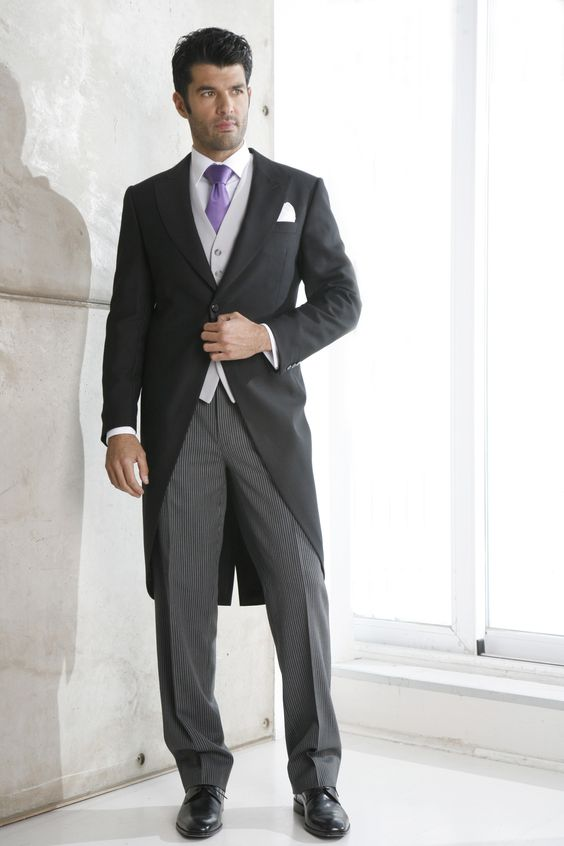 The purple tie stands out with this evening tail suit for a black tie wedding.