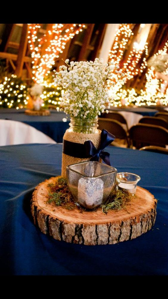 Baby's breath, votives, moss, wood slices and mason jars for an adorable and rustic centerpiece in navy blue and white. Photo: Gloria Adele Photography.