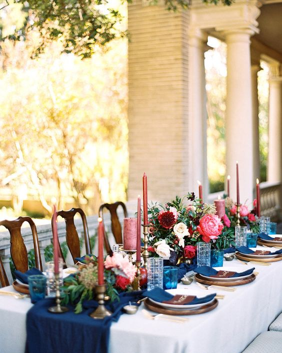 Bright pops of fuchsia color against a navy blue wedding tablescape at a Historic Texas home. Photo: Charla Storey Photography.