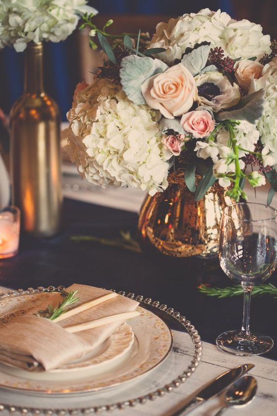 Vintage weddings can leverage from gold blush and navy blue color schemes. Love the greenery details on each table setting.