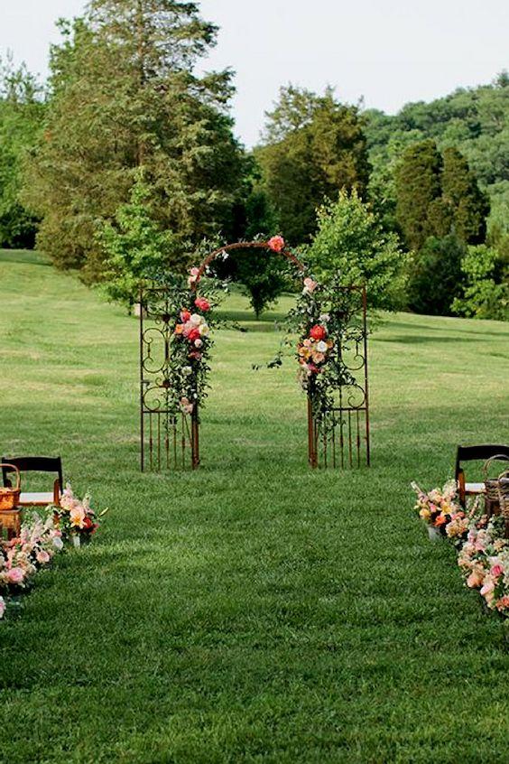 Puerta de hierro forjado decorada con flores para una boda en el jardín. Deja lucir a la naturaleza.