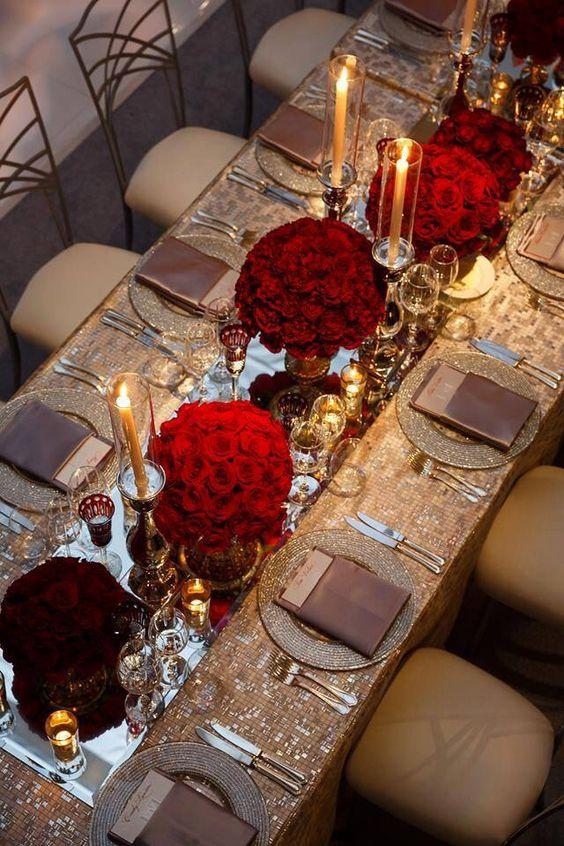 Mesa larga con espejos y arreglos de flores en rojo tomate.
