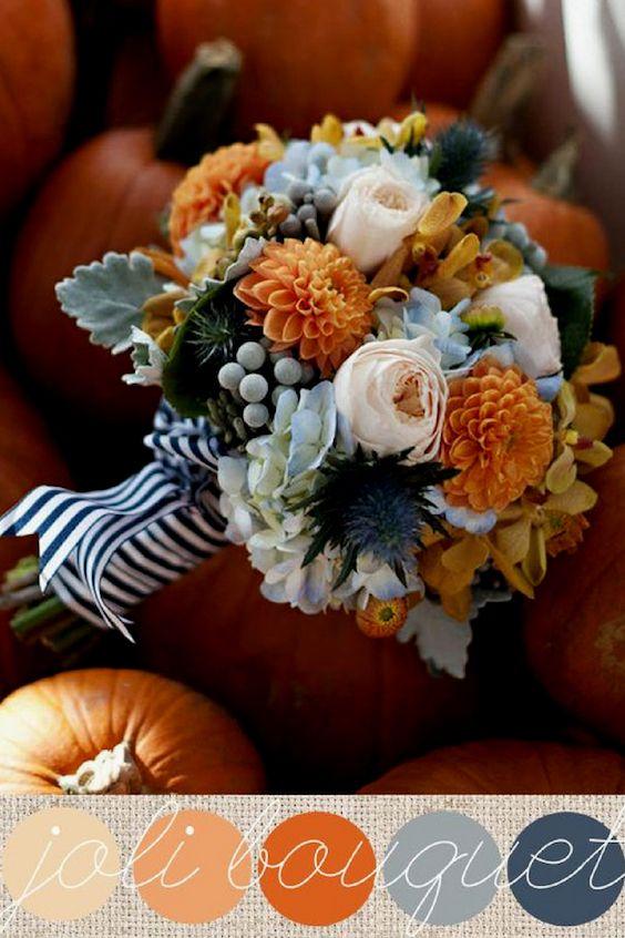 Un ramo nupcial que mezcla orquídeas, dalias, rosas, hortensias, cardos azules, bayas y hojas de cineraria con dulces colores azules, anaranjados y grises.