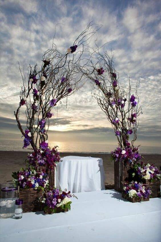 El ultravioleta luce fabuloso con el blanco en este arco de bodas con ramas.