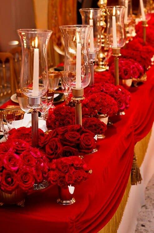 Centros de mesa para boda en rojo con arreglos florales bajos mientras los candelabros dan la altura sin bloquear la vista de los invitados.
