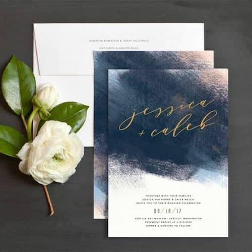 Invitación muy moderna con pinceladas en azul y toques en rosa con caligrafía en dorado siguiendo las tendencias en invitaciones de boda 2018 de Elli.