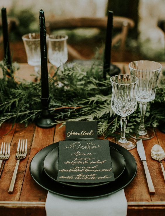 Moody forest weddings are all the rage right now. Style your table with an evergreen runner, crystal glasses and tall dark tapered candles.