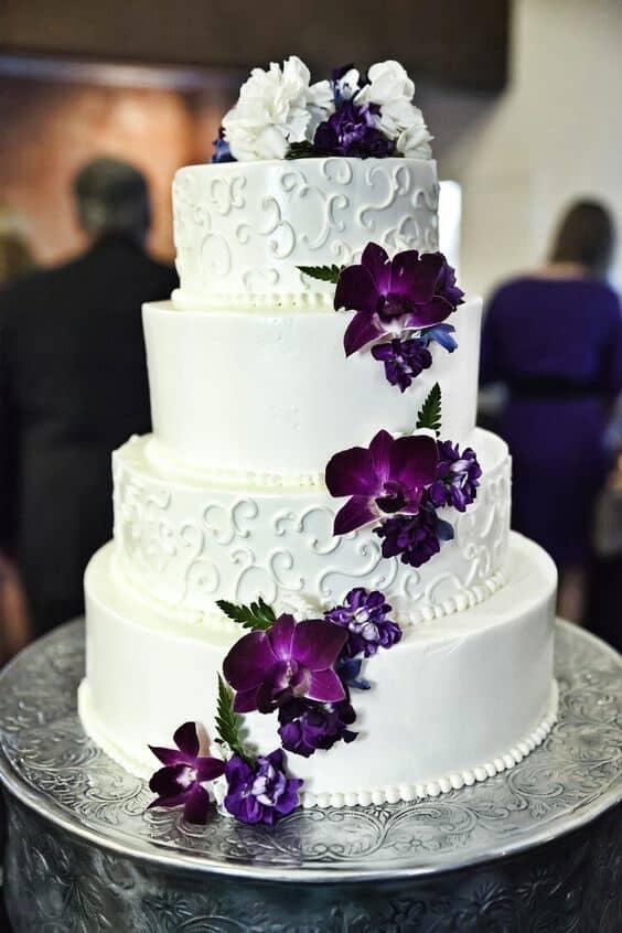 Flores en morado en cascada sobre un pastel de bodas en blanco. Bello Romance Photography.