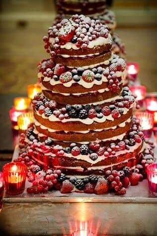 Frutos rojos en el pastel de una boda íntima invernal iluminada con velas en vasitos rojos.