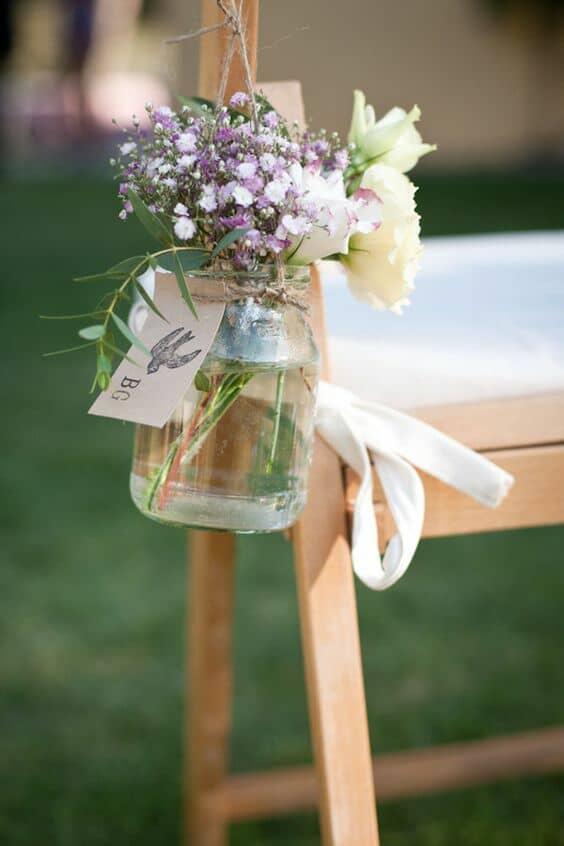 Pequeños ramos de lavanda en las sillas dentro de los famosos mason jars con cuerdas de arpillera.