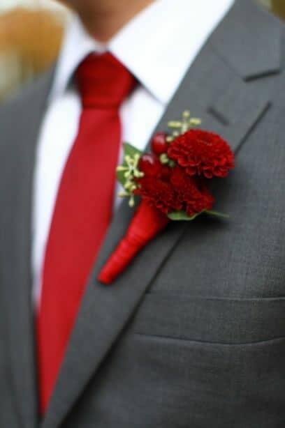 Corbata en rojo tomate y boutonnieres con dalias para el novio y sus padrinos. Tamara Reid Designs.