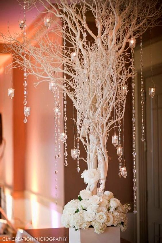 A bundle of sticks, silver paint, hanging chains and white flowers to craft a stunning wedding centerpiece. Cly Creation Photography.