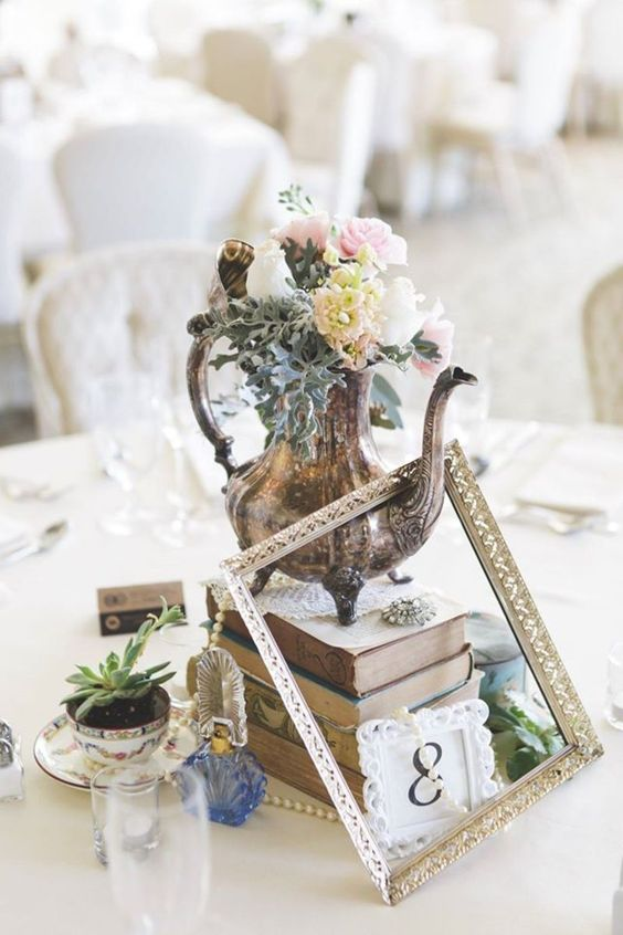 It's not just vintage, it's ultra romantic vintage. To build this glorious centerpiece get a hold of a silver teapot, pearls, perfume bottles, lace, teacups, succulents and an empty frame.
