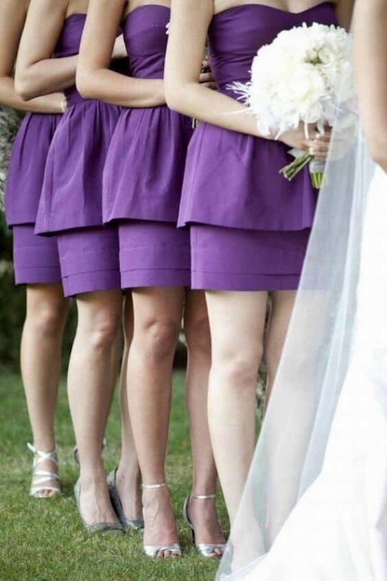 Vestidos cortos para damas de honor en ultravioleta con ramos blancos de hortensias.
