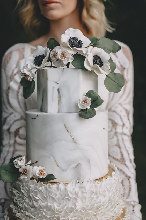 Stunning wedding cake with delicate piping and the top two tiers imitating marble with posies and eucalyptus leaves for a boho wedding at an industrial venue.