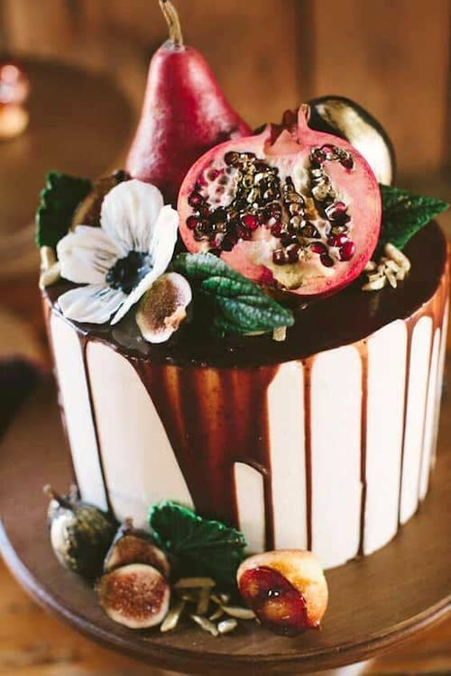Autumn enchanted forest drip wedding cake with figs, pears, pomegranates and posies for an intimate outdoor ceremony in Maine. Cake by Erin Gardner. Photo: Henry + Mac Photography.