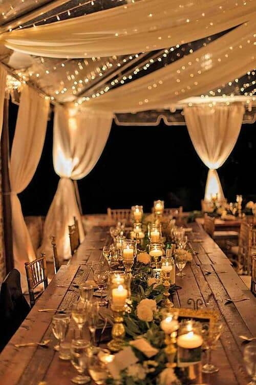 Tented outdoor beach wedding reception lighting.