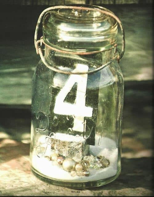 Love this for a beach wedding. Mason jars filled with sand, seashells and a card table number held by a cork or wood sliver.