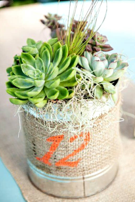 Centerpiece and table number all in one for a rustic wedding. Who doesn't love succulents?
