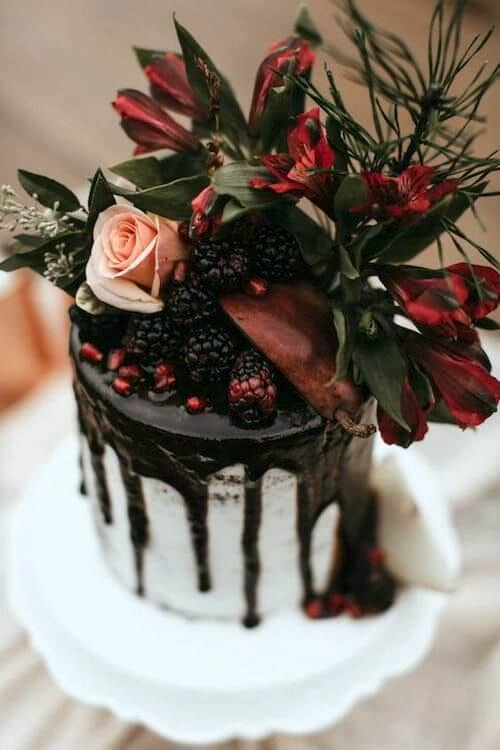 Winter sets the tone with this berry red drip enchanted forest themed wedding cake. Photo: B. Matthews Creative.
