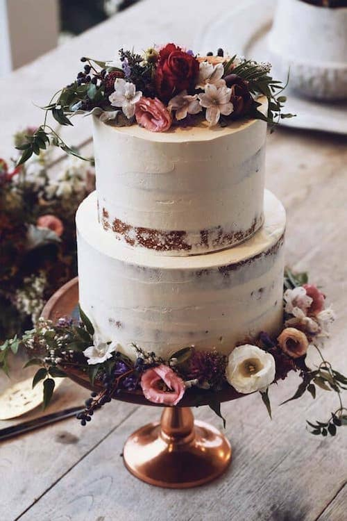 Deep moody colors surround half naked enchanted forest themed wedding cakes.