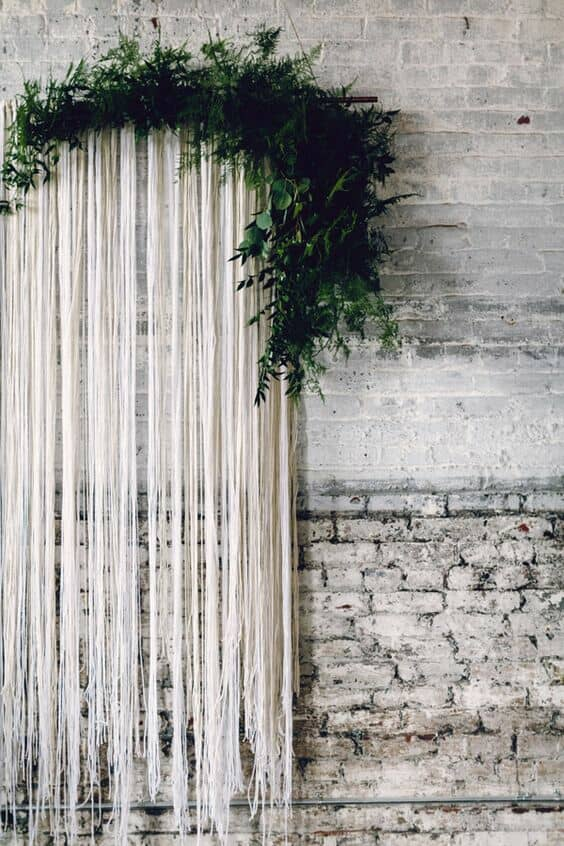 Raw spaces go hand in hand with innovative wedding photo booth ideas. Streamer backdrop with greenery. Photo: Danfredo Photos and Film.