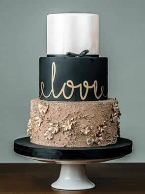 The addition of metallics to this forest cake makes all the difference. Absolutely mesmerized by the bottom tier that bears some elaborate work with oak leaves and roses.