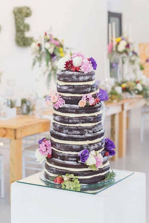 Pink, red tomato and ultraviolet pops of color on this naked woodland wedding cake by Adele Kloppers.