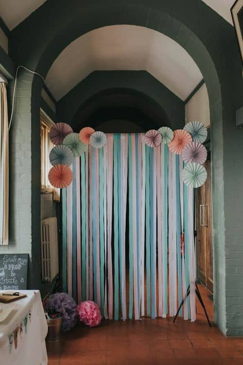 Photo booth ideas with ribbon paper and pinwheels in pastel tones. Find a door, tie a rope to both sides and start working your magic. And yes, you can get through it.