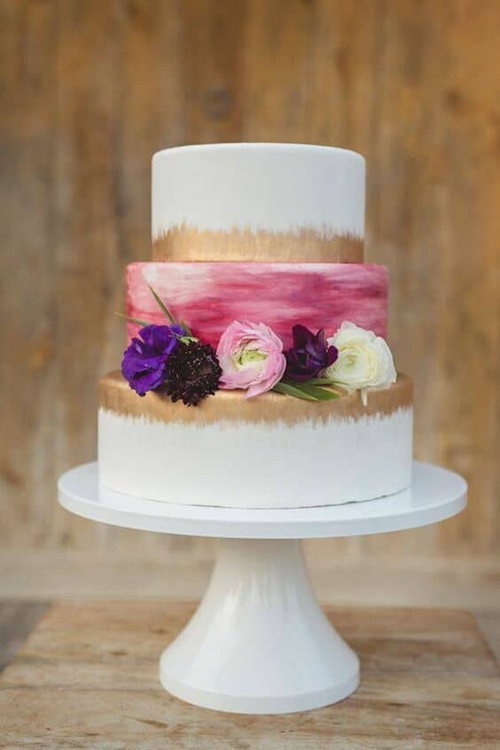 Watercolors. gold foil and ultra violet flowers for a summer forest themed wedding cake. Alyssa Turner Photography.