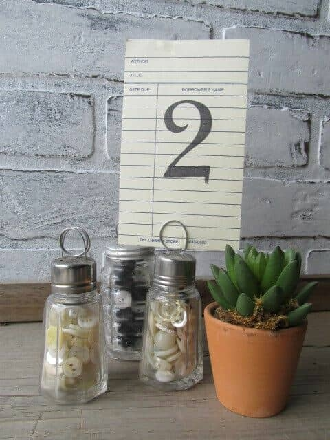 Transform your salt and pepper shakers into table number holders. Fill them up with buttons or shells so they don't fall from the number's weight.