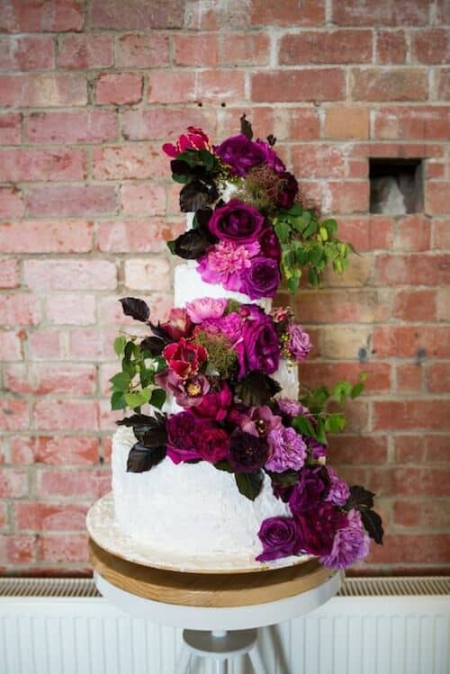 Traditional three tiered wedding cake with fresh flowers in magenta and plum that spells summer in the forest.