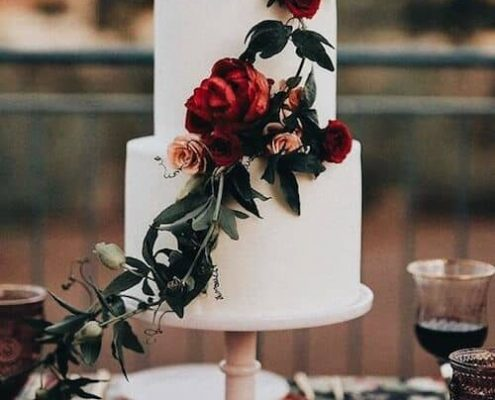 Love the contrast of the moody color palette against the white wedding cake! Photo: Jonnie and Garrett.