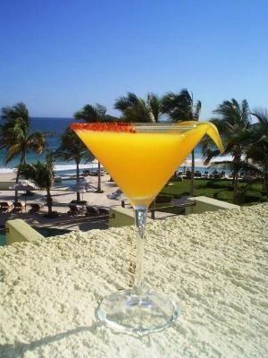 Recibe a tus invitados en la playa con un mango Martini. Mango rum, peach schnapps, Cointreau de naranja, zumo de arándanos, zumo de piña.