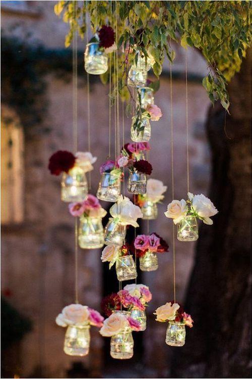 Decoraciones sencillas y económicas para una boda veraniega en el bosque. Delicados frascos llenos de luces LED y delicadas flores. Perfectas para crear una atmósfera íntima como de bosque.