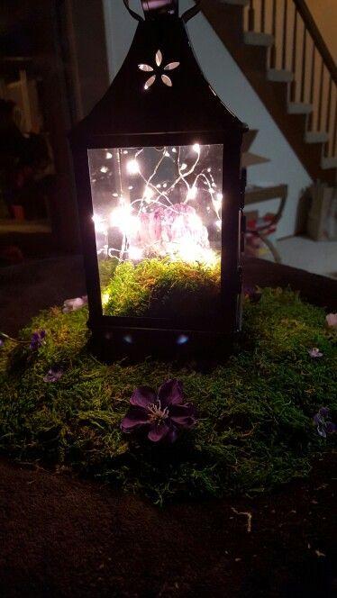 Centro de mesa con musgo, ametistas y luces LED en violeta y verde que da la ilusión de cuento de hadas.