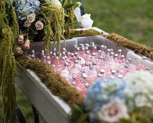 Una manera original de servir las bebidas a la hora del cóctel en una carretilla con mini botellitas decorada con musgo, hortensias y amapolas.