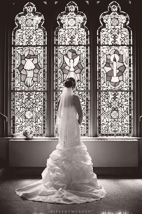Foto de la Novia. Frente a un vitral de la iglesia. Crédito de foto: Tiffany Murray Photography.