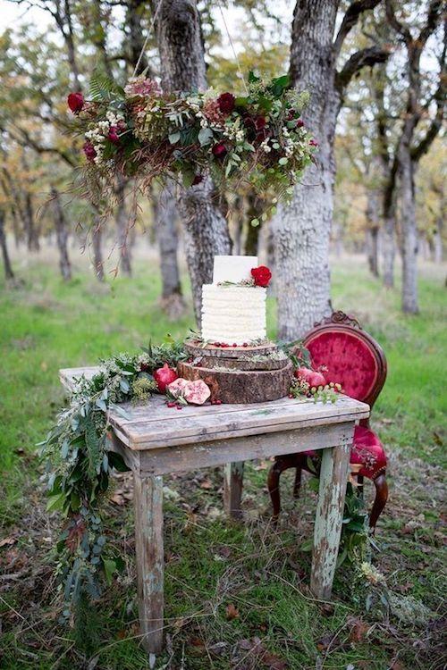Sostén de tarta en madera, laureles, rosas rojas y un sillón antiguo en color rubí unen lo rústico de la naturaleza a lo vintage.