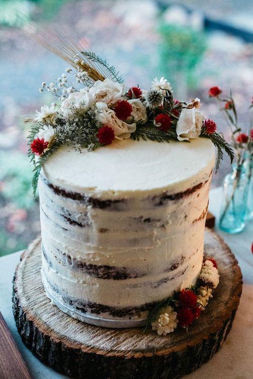 Tarta semi desnuda con flores frescas en blanco y rojo para una boda íntima de cuento de hadas. Foto: Erin Wheat Photography.