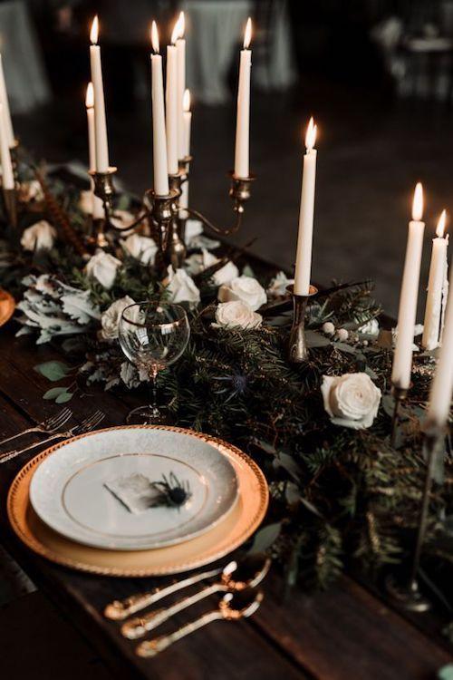 Ramas de pino, rosas blancas, candelabros y posa-platos en dorado incorporan la temática (y el olor) del bosque a tu boda. Foto: Keicy Leigh Photography.