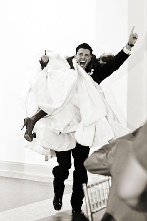 Tradiciones de Bodas para Alejar los Malos Espíritus. Descubre porque cargar la novia en brazos es una de las tradiciones de bodas. Simpática y preciosa foto del novio llevando a la novia sobre el hombro.
