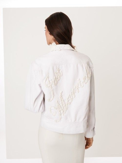 La chaqueta denim blanca de Oscar de la Renta es ideal para las novias mas cool. Con delicados apliques florales en el cuello y un bordado en estilo retro perfecta para el día de tu boda o para tu luna de miel.