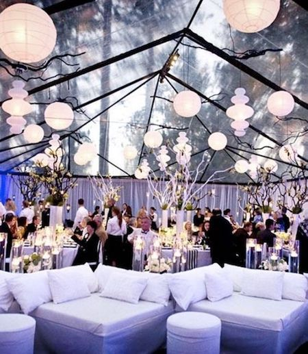 Clear tented wedding reception illuminated with globes and white curtains all around, highlight the modern lounge decor.