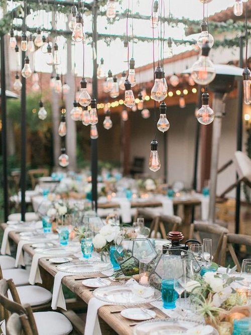 A rustic look with Edison lightbulbs hanging from the structure of a clear wedding tent in Southern California.