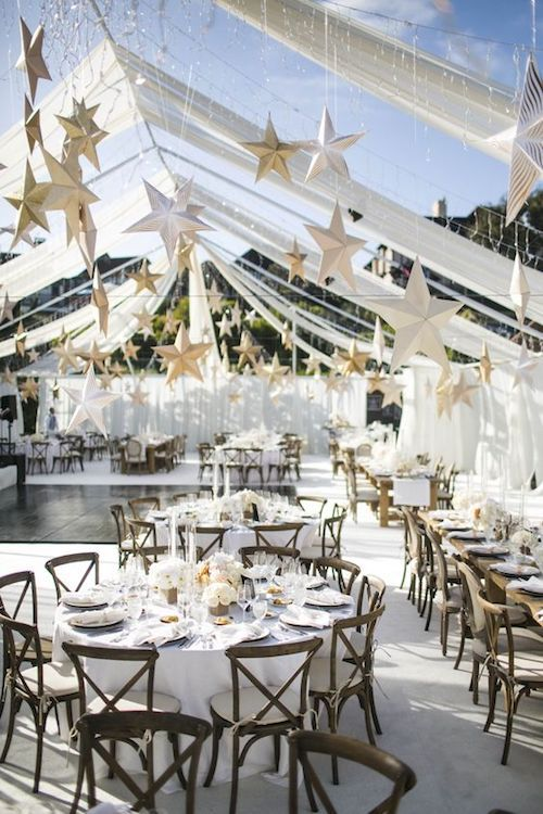 Elegant reception space with white drapery and rustic wooden tables. White and gold paper stars hanging from invisible threads. Photo: Samuel Lippke Studios.