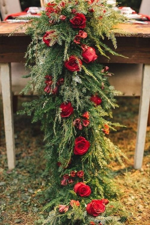 Gorgeous evergreen and red roses wedding table runner ideas. Forget the linens and go for this breathtaking table decor!