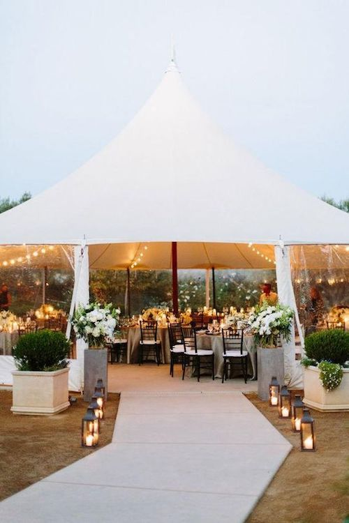Lush garden celebration with pole tent filled with lots of greenery, string lights and lanterns.