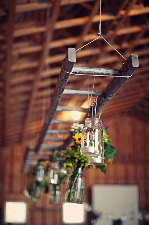 Florals in bottles and mason jars hanging from a ladder above the wedding tables.